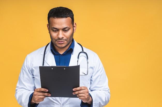 Sorridenti african american indian medico nero uomo ricetta di scrittura negli appunti, isolate su sfondo giallo.