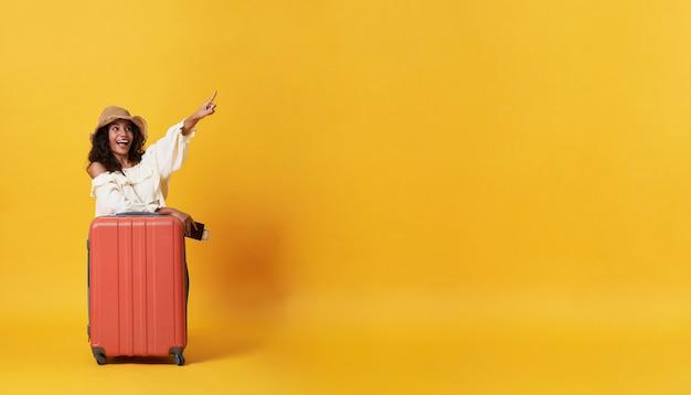 La donna africana sorridente felice si è vestita in vestiti dell'estate con bagagli che godono della loro vacanza di vacanze estive nel giallo con lo spazio della copia.