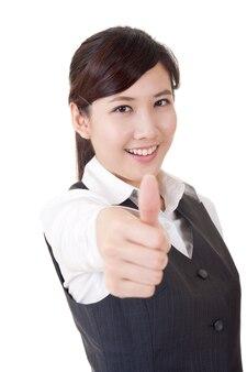 La donna asiatica sorridente felice di affari gli dà un segno eccellente, ritratto del primo piano su fondo bianco.
