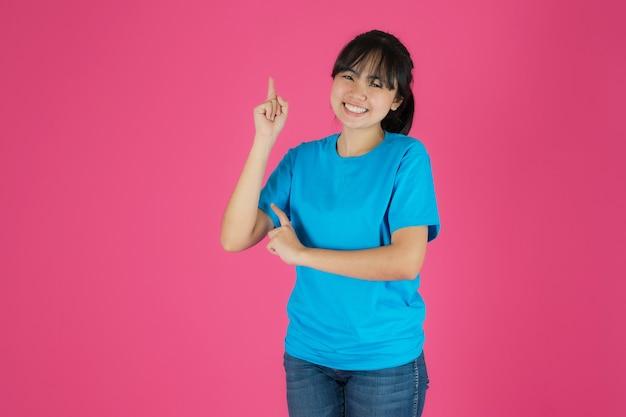 Ragazza asiatica sorridente felice che sta su fondo rosa
