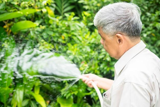 L'uomo anziano anziano asiatico felice e sorridente sta innaffiando le piante