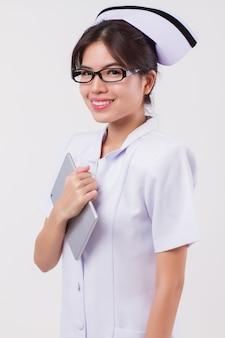 Compressa asiatica felice e sorridente del computer della tenuta dell'infermiera della donna; ritratto isolato studio dell'infermiera femminile asiatica nell'espressione positiva, amichevole, felice, sorridente con la compressa; modello di giovane donna adulta asiatica degli anni '20