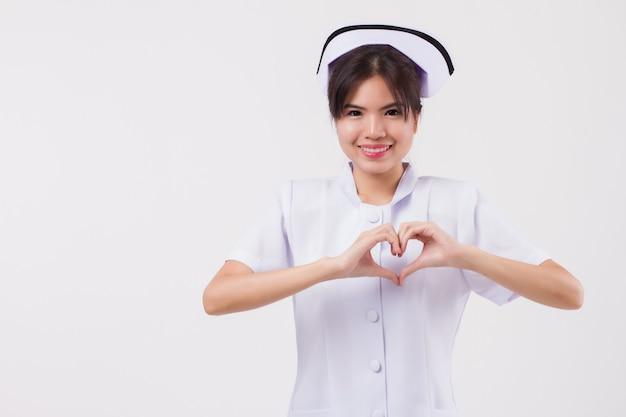 Infermiera asiatica sorridente felice della donna con il gesto della mano del cuore