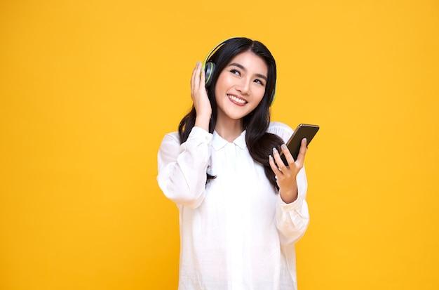 Donna asiatica sorridente felice che indossa le cuffie senza fili che ascolta la musica con lo smartphone sulla parete gialla luminosa.