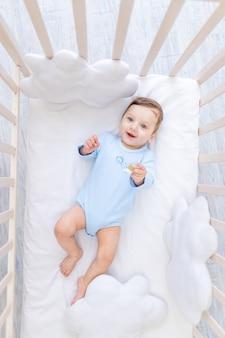 Neonato sorridente felice nella culla in tuta blu, piccolo bambino gioioso carino in camera da letto