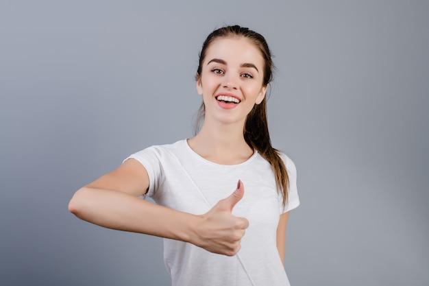 Bella ragazza castana sorridente felice che mostra i pollici su isolati sopra grey