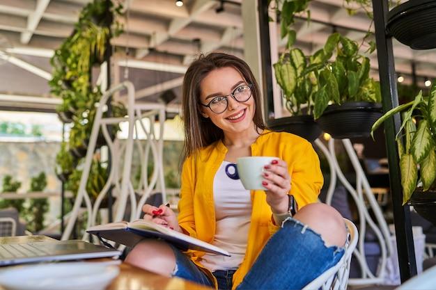 Bella donna sorridente felice che si siede e che beve caffè.