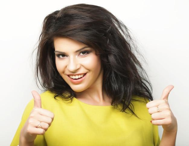 La bella giovane donna sorridente felice che mostra i pollici aumenta il gesto
