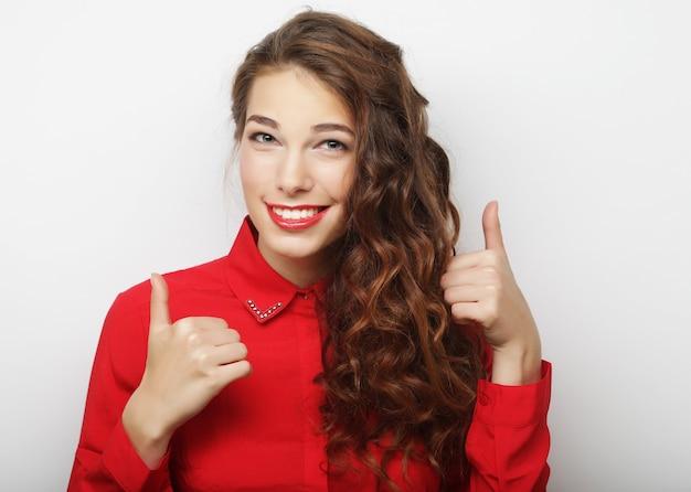 Bella giovane donna sorridente felice che mostra i pollici in su gesto