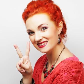 Bella giovane donna sorridente felice che mostra due dita o gesto di vittoria victory