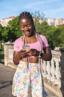 Donna dell'africa nera sorridente felice che chiacchiera sul suo telefono cellulare in un parco pubblico in una giornata di sole con cielo blu. stile di vita della donna di moda nera