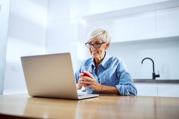Donna senior bionda sorridente felice che si siede al tavolo da pranzo, bevendo vino rosso e avendo video chiamata sopra al computer portatile
