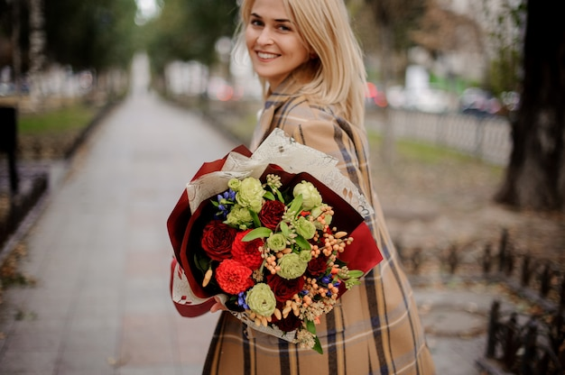 Donna bionda sorridente felice in cappotto del plaid che tiene un mazzo luminoso di fiori che cammina sul vicolo