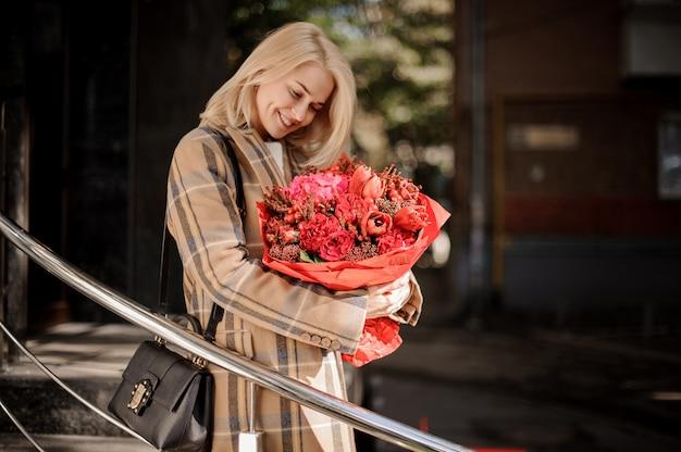 Donna bionda felice e sorridente in cappotto a quadri con un grande mazzo di fiori rosso