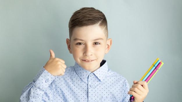 Ragazzo sorridente felice. bambino dalla scuola elementare in uniforme. ragazzo divertente Foto Premium