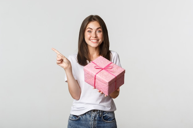 Ragazza castana sorridente felice che tiene regalo di compleanno e dito puntato a sinistra al logo