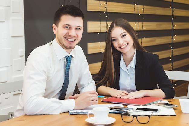 Coppia di affari sorridente felice che guarda l'obbiettivo