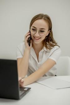 Donna di affari sorridente felice che ha una chiamata di lavoro, discutere di riunioni, pianificare la sua giornata di lavoro, utilizzando lo smartphone