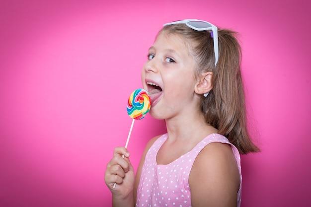 Bambino sorridente felice con dolce lecca-lecca che si diverte su una superficie rosa colorata colorful