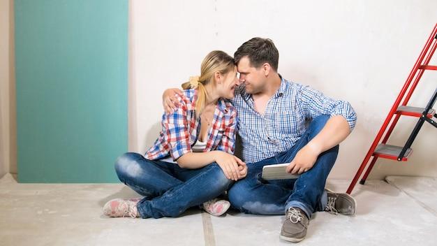 Felice coppia sorridente che abbraccia e abbraccia nella nuova casa in fase di ristrutturazione.