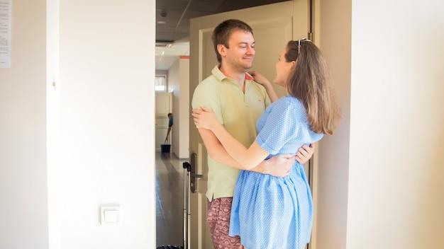 Felice coppia sorridente che si abbraccia e si guarda dopo essere arrivata in hotel durante le vacanze estive