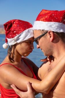 Le coppie sorridenti felici nell'amore celebrano il natale e il nuovo anno al mar rosso.