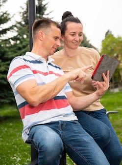 Coppia sorridente felice utilizzando una tavoletta digitale all'aperto nel parco