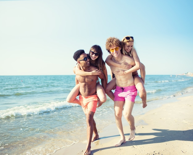 Coppie sorridenti felici che giocano sulla spiaggia
