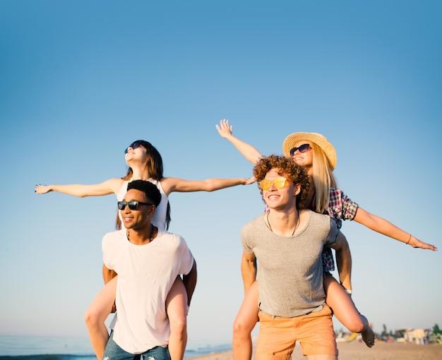 Coppie sorridenti felici che giocano sulla spiaggia assolata