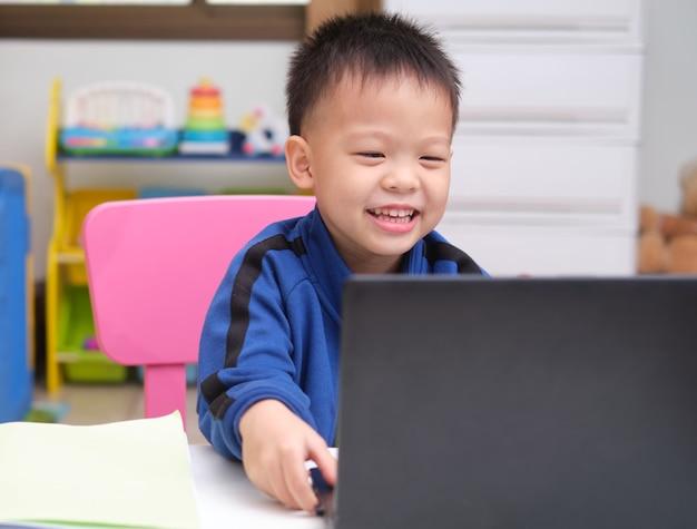 Piccolo bambino asiatico sveglio sorridente felice con il computer portatile del taccuino che effettua la videochiamata a casa