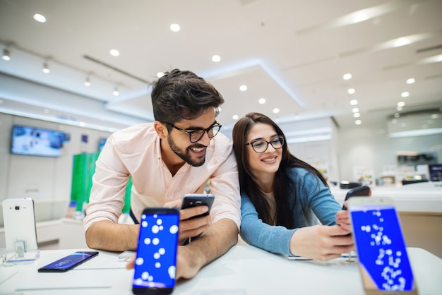 Giovani coppie sveglie sorridenti felici in deposito elettronico. possedere nuovi telefoni e testarli.