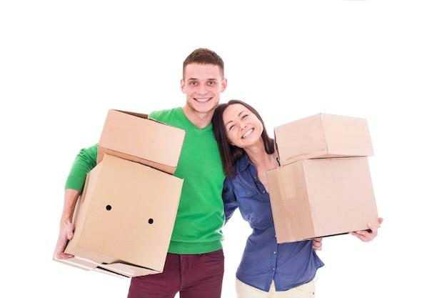 Felice consegna sorridente uomo e donna che trasportano scatole isolate su sfondo bianco. la coppia ha un ordine per la spesa