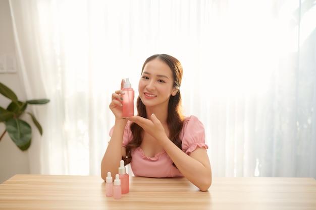 Donna elegante sorridente felice o blogger di bellezza con lozione durante la registrazione di video