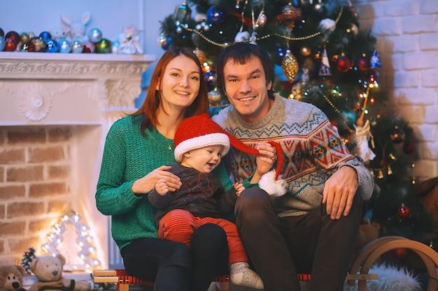 Famiglia sorridente felice all'interno di una casa sullo sfondo dell'albero di natale con regali