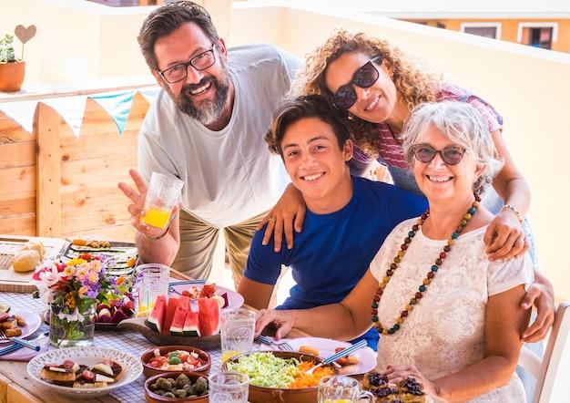 Famiglia felice e sorridente, multigenerazionale. coppia con figlio e nonna che si godono il brunch o un pasto insieme. la luce del sole sul campo della terrazza