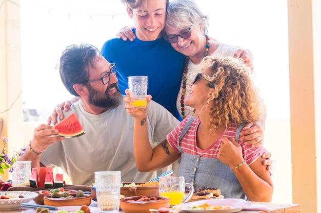 Famiglia felice e sorridente, multigenerazionale. coppia con figlio e nonna che si godono cibo e bevande insieme. quattro persone che festeggiano la festa