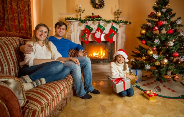 Famiglia sorridente felice che posa al soggiorno decorato per il natale con il camino bruciante