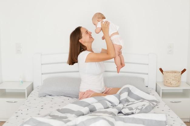 Felice donna sorridente che indossa una maglietta bianca in stile casual che tiene in mano la bambina mentre è seduta sul letto in una stanza luminosa, la mamma trascorre del tempo con il suo neonato.