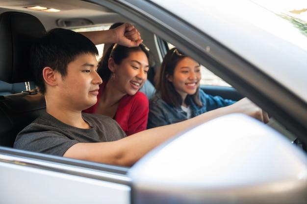 Amici sorridenti felici in macchina guardano film in tv o controllano la mappa del navigatore gps mentre guidano un veicolo suv.