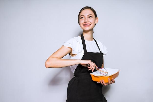 Cuoco unico sorridente felice in grembiule nero che prepara una torta deliziosa