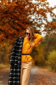 Felice ragazza sorridente in abiti autunnali alla moda con maglione vintage giallo, cappotto nero e occhiali da sole cammina nel parco con fogliame autunnale colorato