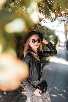 Una ragazza sorridente felice in look alla moda con occhiali da sole e un cappello con una borsa alla moda sta camminando nella giornata di sole autunnale