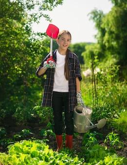 Ragazza sorridente felice che posa al giardino con la vanga e l'annaffiatoio
