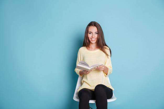 Felice ragazza sorridente che legge un libro e si siede sulla sedia isolata sullo sfondo blu blue