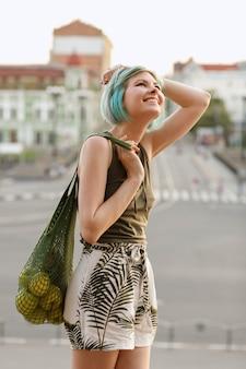 Ragazza sorridente felice con un sacchetto di frutta sulla sera d'estate in città