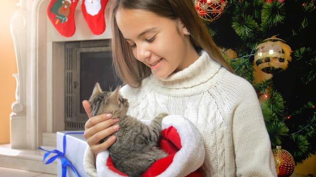 Ragazza sorridente felice con il gatto al camino e all'albero di natale