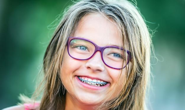 Ragazza sorridente felice con l'apparecchio per i denti giovane ragazza bionda caucasica carina che indossa l'apparecchio per i denti