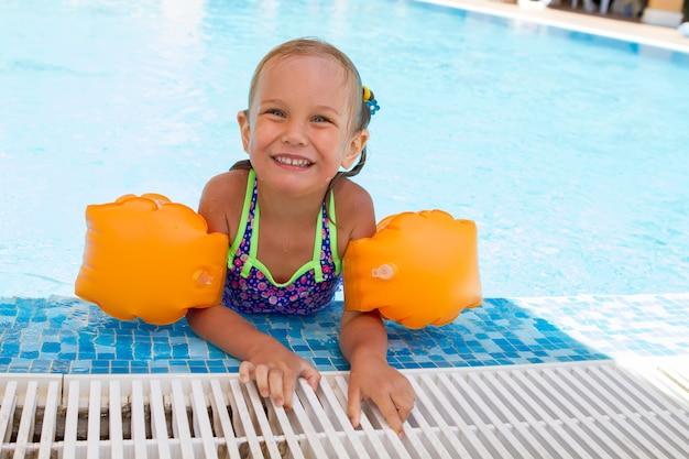 Ragazza sorridente felice con i galleggianti in braccio divertendosi e giocando in piscina