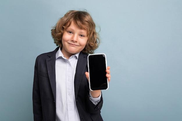 Ragazzo positivo bello sorridente felice con il telefono d'uso della tenuta del vestito dai capelli ricci biondi