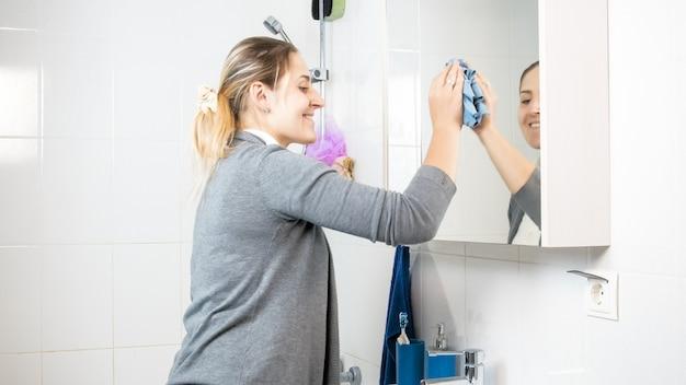Casalinga sorridente felice che fa pulizia inbagno e lava lo specchio sporco.